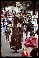 Papier-mache tree marches amid adults and kids in Earth Day parade at Forest Park, St. Louis Missouri