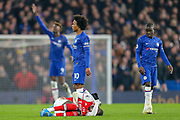 Arsenal forward Nicolas Pépé (19) on the ground in apparent pain following a challenge during the Premier League match between Chelsea and Arsenal at Stamford Bridge, London, England on 21 January 2020.
