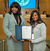 Energize for E-STEM Academy Southeast principal Argentina James, left, presents Comcast representative Misha McClure with a commendation during a Houston ISD Board of Education meeting, December 12, 2013.