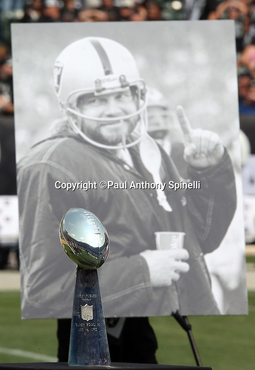 A Super Bowl X Trophy stands in front of a photograph of recently deceased Oakland Raiders quarterback Kenny Stabler during a halftime tribute to the former Raider during the 2015 NFL week 1 regular season football game against the Cincinnati Bengals on Sunday, Sept. 13, 2015 in Oakland, Calif. The Bengals won the game 33-13. (©Paul Anthony Spinelli)