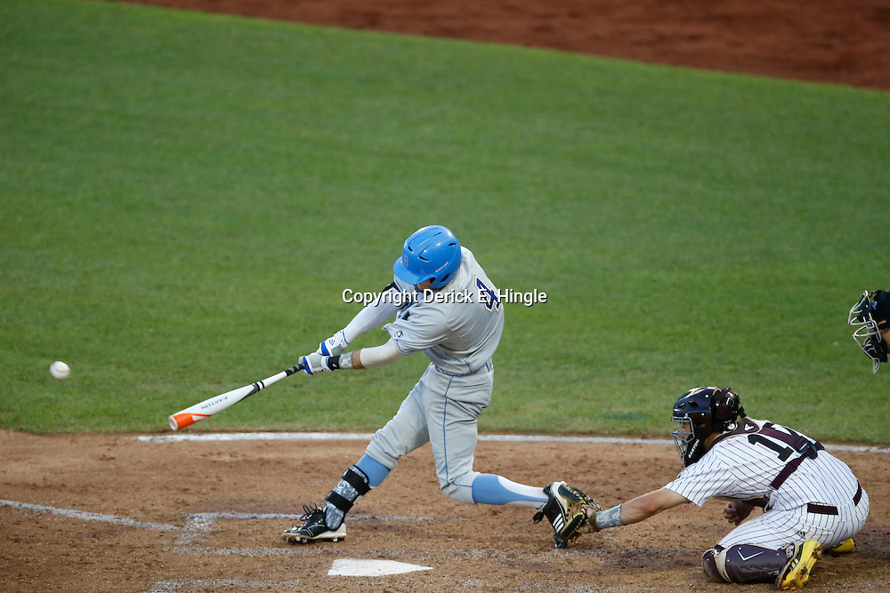 Jun 24, 2013; Omaha, NE, USA; UCLA Bruins right fielder Eric Filia (4) hits a two-RBI single during the fourth inning in game 1 of the College World Series finals in front of Mississippi State Bulldogs catcher Nick Ammirati (right) at TD Ameritrade Park. Mandatory Credit: Derick E. Hingle-USA TODAY Sports