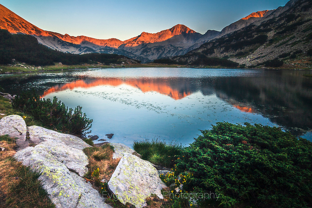 Mountain range reflections colored in red in a lake
