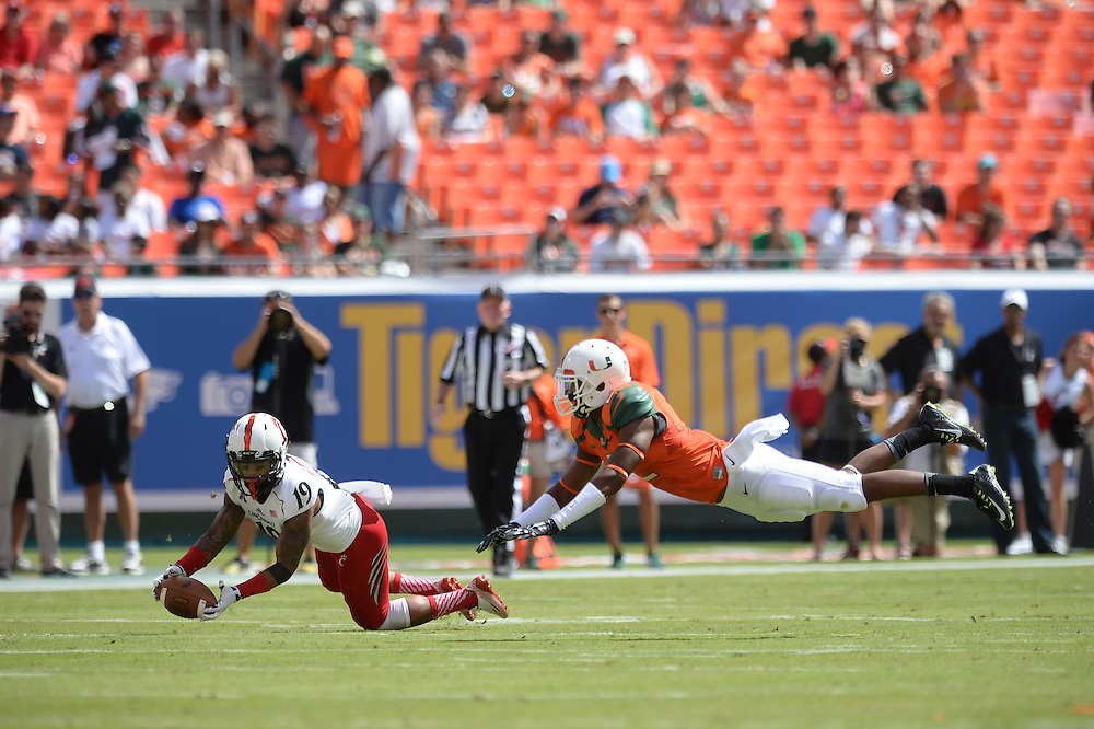 October 11, 2014: Shaq Washington #19 of the Cincinnati Bearcats tries to catch a pass as Deon Bush #2 of the Miami Hurricanes provides coverage during the football game between the Cincinnati Bearcats and the Miami Hurricanes at Sun Life Stadium in Miami Gardens, FL. The Hurricanes defeated the Bearcats 55-34.