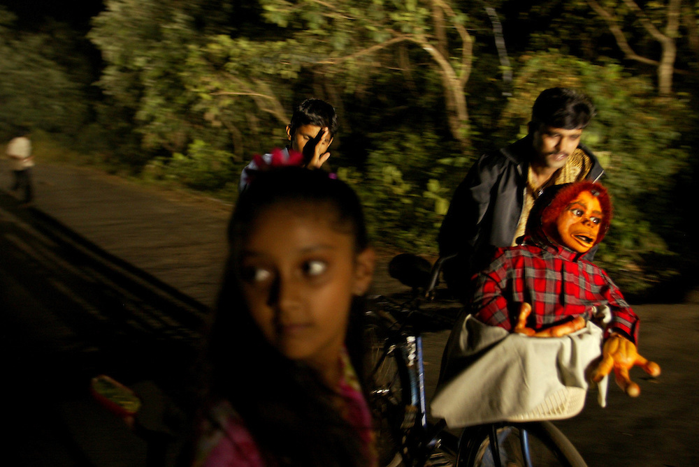"The Puppet of ""Hanu"" an ET Indian like character is taken by a prop assistant to the top of a hill, as a child actress waits for him to do a  the retake of a scene in Film City in the outskirts of Bombay, India Dec. 7, 2004. Bombay's film industry may be the most prolific in the world, but unlike it's American counterpart, much of the work is done on a shoestring. The city churns out hundreds of films a year on its celluloid production line."