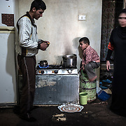A syrian couple prepares tea for their relatives, on december 22nd 2013 in their appartment in Irbid.