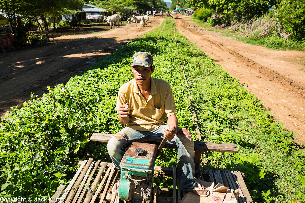 29 JUNE 2013 - BATTAMBANG, CAMBODIA:  A bamboo train driver near Battambang. The bamboo train, called a norry (nori) in Khmer is a 3m-long wood frame, covered lengthwise with slats made of ultra-light bamboo, that rests on two barbell-like bogies, the aft one connected by fan belts to a 6HP gasoline engine. The train runs on tracks originally laid by the French when Cambodia was a French colony. Years of war and neglect have made the tracks unsafe for regular trains.  Cambodians put 10 or 15 people on each one or up to three tonnes of rice and supplies. They cruise at about 15km/h. The Bamboo Train is very popular with tourists and now most of the trains around Battambang will only take tourists, who will pay a lot more than Cambodians can, to ride the train.       PHOTO BY JACK KURTZ