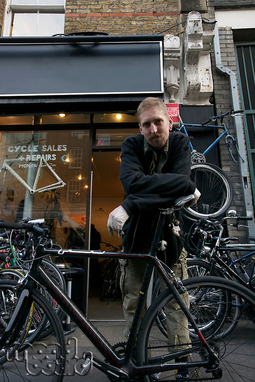 Portrait of mid adult man standing outside cycle shop