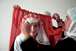 Sunday: Nazim's younger sister gets ready for the procession that will bring the clothes for Fatme and her family to Fatme's house, it's the tradition for her to wear white headscarf with the red flowers covered in a red shall, similar to what the bride Fatme will wear but without the face paint, glitter and tinsels