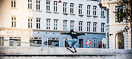 A skateboarder doing a trick with his skateboard on the streets of Copenhagen.