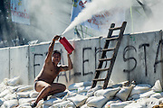 01 DECEMBER 2013 - BANGKOK, THAILAND: An anti-government protestor in his underwear takes cover behind a concrete barricade while he uses a fire extinguisher against Thai riot police. Thousands of anti-government Thais confronted riot police at Phanitchayakan Intersection, where Rama V and Phitsanoluk Roads intersect, next to Government House (the office of the Prime Minister). Protestors threw rocks, cherry bombs, small explosives and Molotov cocktails at police who responded with waves of tear gas and chemical dispersal weapons. At least four people were killed at a university in suburban Bangkok when gangs of pro-government and anti-government demonstrators clashed. This is the most serious political violence in Thailand since 2010.    PHOTO BY JACK KURTZ