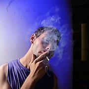 A 22-year-old man smokes cigarettes, Tucson, Arizona, USA.
