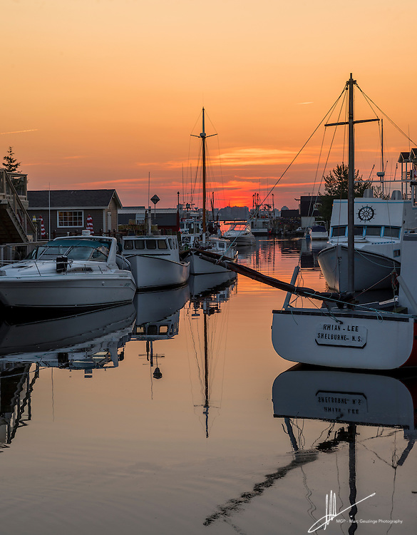 Calm waters reflect the boats in Eastern Passage Harbour just after sunset. The Halifax skyline can be seen in the distance.
