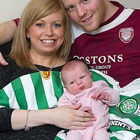 Arbroath defender Mark Baxter pictured with his partner Natasha Gow and their 2 week old daughter Eva. Mark almost missed the Celtic v Arbroath Scottish Cup game at parkhead due to the birth of his daughter..   Eva is pictured laying on Beram Kayal's shirt that Mark got on the evening as a momento.<br /> Picture by Graeme Hart.<br /> Copyright Perthshire Picture Agency<br /> Tel: 01738 623350  Mobile: 07990 594431