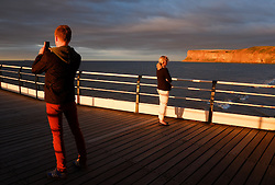 © Licensed to London News Pictures.06/08/15<br /> Saltburn, UK. <br /> <br /> A couple stand on the pier at sunset at Saltburn by the Sea in Cleveland. <br /> <br /> Photo credit : Ian Forsyth/LNP