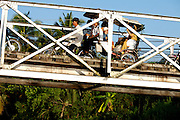 Mekong Delta. Motorbikes on a bridge across a river arm.