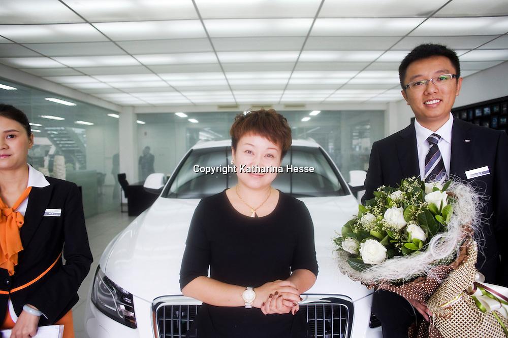 CHENGDU, 10/17/2012 :  Geschaeftsfrau Yang Xi, 37,  mit Audiangestellten vor ihrem neuen Wagen.