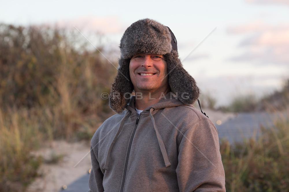 good looking All American middle aged man in a fur hat at the beach in late afternoon light