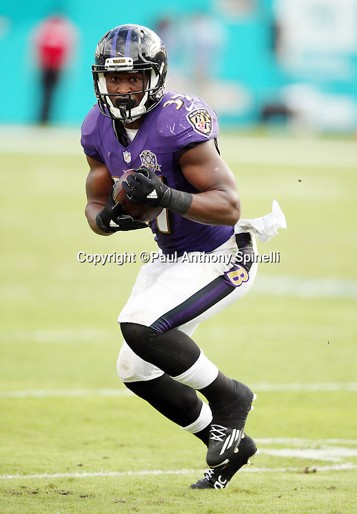 Baltimore Ravens running back Javorius Allen (37) runs with the ball as he catches a 41 yard touchdown pass that cuts the Miami Dolphins third quarter lead to 15-10 during the 2015 week 13 regular season NFL football game against the Miami Dolphins on Sunday, Dec. 6, 2015 in Miami Gardens, Fla. The Dolphins won the game 15-13. (©Paul Anthony Spinelli)