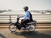 26 FEBRUARY 2015 - PHNOM PENH, CAMBODIA:  A motorcyclist rides over the Cambodia-Japan Friendship Bridge spanning the Tonle Sap River in Phnom Penh.   PHOTO BY JACK KURTZ