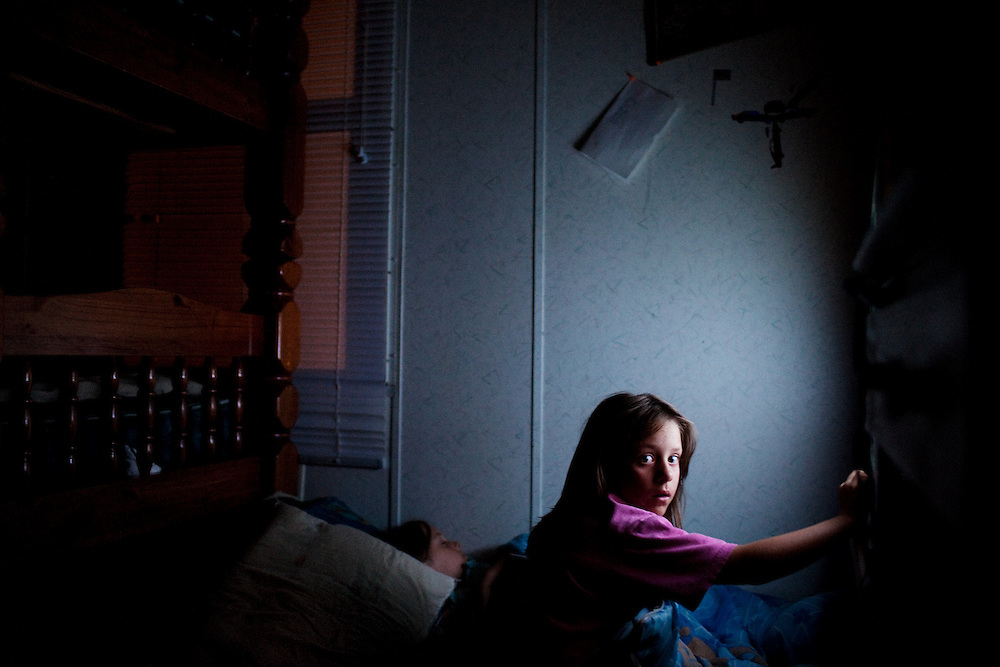 Lacey Sellers, 7, touches the TV screen late at night as her identical twin sister Kacey sleeps next to her on the floor. The girls were born completely deaf and live in the impoverished town of Chauncey, Ohio.