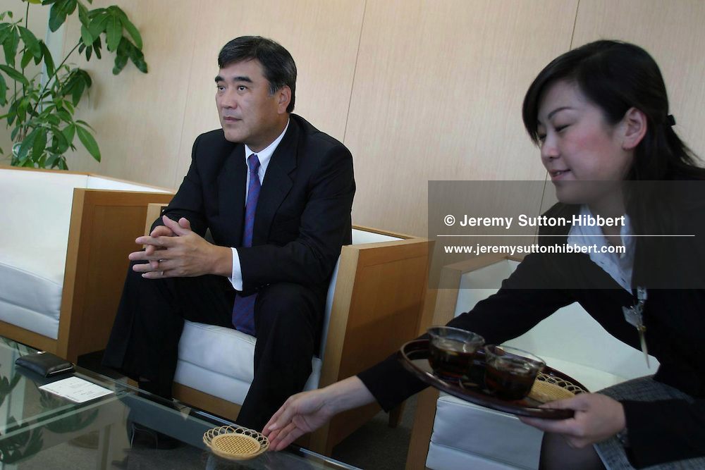 An employee places tea on the table whilst Hideo Sawada, President H.I.S. Co. Ltd (one of the largest travel agencies in Japan), conducts an interview, in Tokyo, Japan, on Thursday, Oct 9th 2003. During interviews it is common for female assistants to enter the rooms silently , bringing refreshment drinks of green tea, coffee, or orange juice, to the company head and his guests.