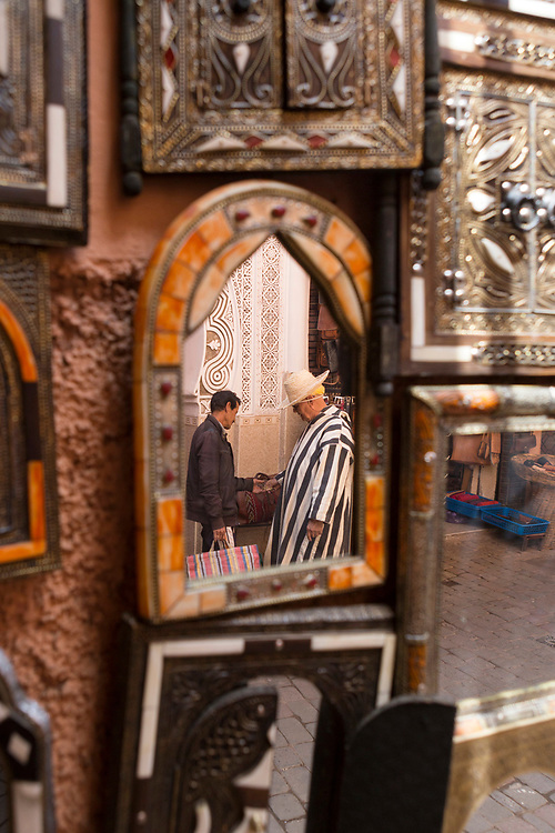 MARRAKESH, MOROCCO - May 27th 2018 - Reflections of street life and architecture framed in mirrors hanging on the wall in the Marrakesh medina, Morocco