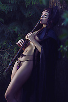 Artistic sensual portrait of a beautiful sexy Native American tribal woman playing a bamboo flute in the nature with her half nude body shining in dim light