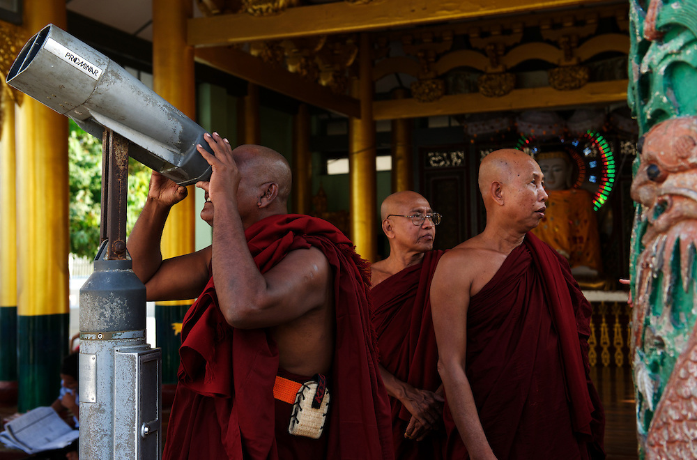 Buddhist monks visiting Shwedagon Pagoda use a telescope to view details of the bejewelled upper tiers of the mighty pagoda.<br /> <br /> hwedagon Zedi Daw The, as it is known locally,or The Crown of Burma less formally, is rumoured to be the oldest pagoda in the world dating to 2,600 years old. Standing 99m tall and crowning a hilltop, it can be seen from all over Yangon, by day and night.<br /> <br /> The main gold-plated dome is topped by a stupa containing over 7,000 diamonds, rubies, topaz' and sapphires,all offset by a massive emerald positioned to reflect the setting sun.<br /> <br /> As Myanmar's most revered shrine it has always been customary for families and followers of the Buddha to make the pilgrimage to Shwedagon in the same way that Muslims feel compelled to visit the Kaaba at Mecca, at least once in their lifetime.