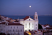 View from Portas do Sol belvederel to Alfama district and a magnificent full moonrise over the Tagus river. In highlights the Santo Estêvão church.This is part of the way of Lisbon's nº28 yellow tram, through the central, most historic region of the city.