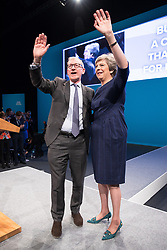 © Licensed to London News Pictures . 04/10/2017. Manchester, UK. Prime Minister THERESA MAY waves from the stage alongside her husband PHILIP MAY after Theresa May delivers her keynote speech on the fourth and final day of the Conservative Party Conference at the Manchester Central Convention Centre . Photo credit: Joel Goodman/LNP