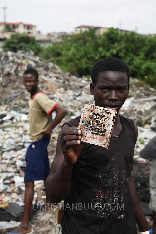Electronic waste export to Nigeria...Alaba International Market, one of the largest markets for electronic goods in West Africa.  New and old - and a lot of non-working electronic goods such as TVs and computers come in to the market via Lagos harbour from the US, Western Europe and China...Kids showing what can be found on the neaby dump, old printer circuit boards, old TV casings and lots of CRT glass...The shipment - TV-set originally delivered to municipality-run collecting point in UK for discarded electronic products - was tracked and monitored by Greenpeace using a combination of GPS (Global Positioning System using satellites), GSM (positioning using data from mobile networks to triangulate approximate positions) and an onboard radiofrequency transmitter (used for making triangulations in combination with handheld directional receivers used by team on ground) is placed inside the TV-set.  The TV arrived in Lagos in container no 4629416.