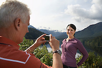 Man photographing woman mountains in background