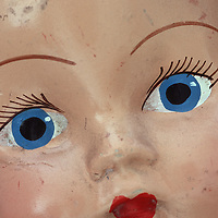 Close up of face of vintage baby doll with big painted blue eyes and red lips and slightly scratched and dirty