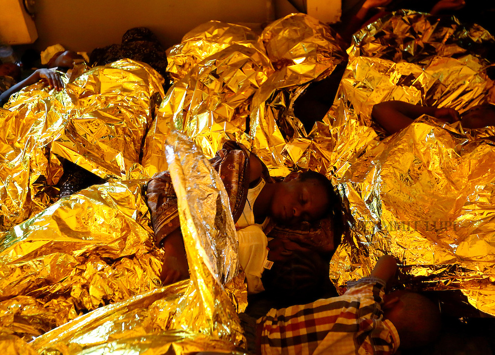 A migrant and her baby, covered with emergency space blankets,  sleep on the deck of the Medecins san Frontiere (MSF) ship Bourbon Argos off the coast of Libya late August 7, 2015.  Some 241 mostly West African migrants on the ship are expected to arrive on the Italian island of Sicily on Sunday, according to MSF.<br /> REUTERS/Darrin Zammit Lupi <br /> MALTA OUT. NO COMMERCIAL OR EDITORIAL SALES IN MALTA