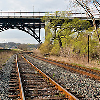 Train tracks curve off into the distance, passing under a steel railway bridge.