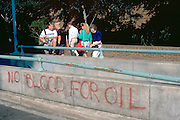 Tourists looking at anti Gulf War graffiti age 75, 21, 17, 16.  Washington DC USA