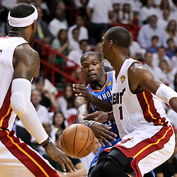 Jun 17, 2012; Miam, FL, USA; Oklahoma City Thunder small forward Kevin Durant (35) passes between Miami Heat power forward Chris Bosh (1) and small forward LeBron James (6) during the first quarter in game three in the 2012 NBA Finals at the American Airlines Arena. Mandatory Credit: Derick E. Hingle-US PRESSWIRE