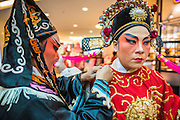 08 FEBRUARY 2013 - BANGKOK, THAILAND:  Chinese opera finish getting into costume before a Chinese New Year performance at Seacon Square in Bangkok. Chinese opera is popular in Thailand and is usually performed in the Teochew language. The weeks surrounding Chinese New Year are important for retailers in Thailand and many malls put on special promotions and events honoring Chinese culture, like Lion Dances or Chinese Opera. Thailand has a large Thai-Chinese population. Millions of Chinese emigrated to Thailand (then Siam) in the 18th and 19th centuries and brought their cultural practices with them.   PHOTO BY JACK KURTZ