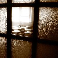 A view through a school door into a classroom with desks