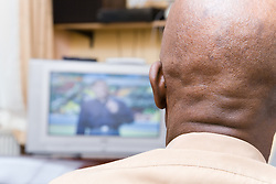 Older man sitting at home watching television