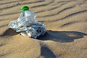 Pllastic bottle pollution on a sandy beach.