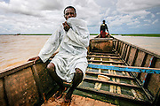 Awalu Garba on a boat trip on Lake Chad. A former fisherman, he switched to driving passengers on his moped from what used to be a harbor in Guité to the new harbor a mile away.  The lake has shrinked to a twentieth of the size it was in 1963, according  to the United Nations Environment Programme. Major overgrazing and unsustainable irrigation projects from all the countries who share border in the area are contributing factors, resulting in loss of vegetation and a drier climate. With a projected temperature increase due to global warming and an advancing Sahara desert, the future does not look good. The picture was taken in 2007, when the boatmen still could access the lake via a connected river. Today the boatmen no longer dare sail for fear of Boko Haram fighters, according to AFP.