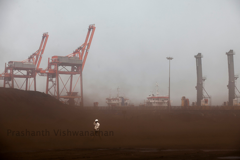 A port worker walks past coal dust rising from trucks transporting Imported coal from Indonasia, at the Krishnapatnam port, in Nellore District, Andhra Pradesh, India, on Friday April 6, 2012. Coal provides 55 percent of India's electricity. Coal production increased just 1 percent in 2011 while power plant capacity jumped 11 percent. Some electricity producers have been importing coal, but that option has become more untenable recently because India's biggest supplier, Indonesia, is raising coal prices. Photographer: Prashanth Vishwanathan