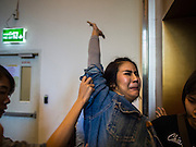 20 NOVEMBER 2014 - BANGKOK, THAILAND: Plainclothes female Thai police officers push NATCHACAH KONG-UDOM into a waiting elevator while arresting her for speaking out against the coup and displaying the three fingered salute from the Hunger Games movies. Kong-Udom was one of at least three people arrested by Thai police during the opening the Hunger Games: Mockingjay - Part 1 in Bangkok Thursday. Opponents of the Thai military coup have adapted the three fingered salute used in the Hunger Games series as a sign of their opposition to the coup. In the weeks before the movie opening Thai police arrested several people for using the Hunger Games salute and Thai media reported that one Thai movie theater chain cancelled plans to show the movie at the request of the military government. There were several small protests at theaters showing the movie Thursday.     PHOTO BY JACK KURTZ