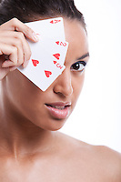 Portrait of young Mixed Race woman covering her eye with playing card against white background