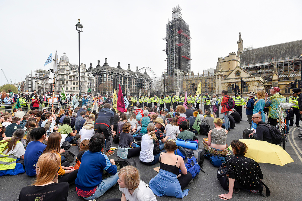 """© Licensed to London News Pictures. 23/04/2019. LONDON, UK.  Activists face police in at Parliament Square during """"London: International Rebellion"""", on day nine of a protest organised by Extinction Rebellion.  Protesters are demanding that governments take action against climate change.  Police have issued a section 14 order for Parliament Square and expect that the occupation of the square will have concluded by the end of the day.  Photo credit: Stephen Chung/LNP"""