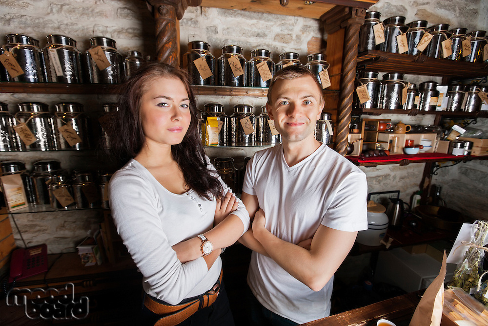 Portrait of confident couple standing arms crossed in tea store