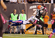 Cleveland Browns wide receiver Josh Gordon (12) catches a 37 yard touchdown pass that ties the score at 24-24in the third quarter while avoiding a diving tackle attempt by Buffalo Bills free safety Aaron Williams (23) during the NFL week 5 football game against the Buffalo Bills on Thursday, Oct. 3, 2013 in Cleveland. The Browns won the game 37-24. ©Paul Anthony Spinelli