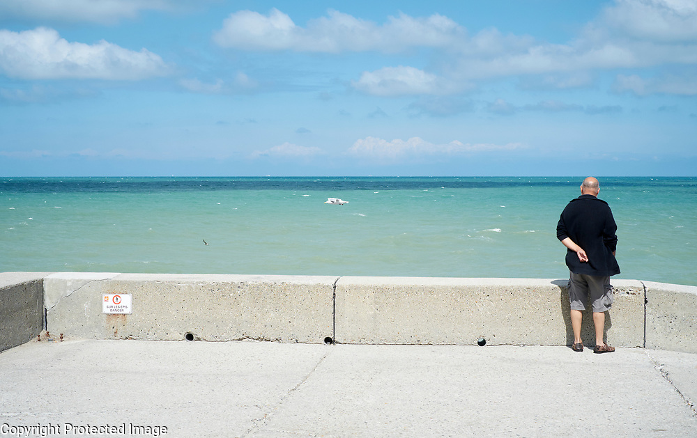 Man kijkt uit over Het Kanaal bij Pourville-sur-mer, Frankrijk - Man is looking over The Channel near Pourville-sur-mer, France