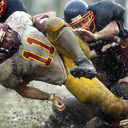 Claremont: Claremont-Mudd-Scripps runningback Ryan Gocong,11, splashes through the rain and mud as the Pomona-Pitzer defense brings him down as Pomona upset Claremont 12-7 at Merritt Field at Pomona College in Claremont,Calif., November 9,2002.<br /> (Pasadena Star-news Staff Photo Keith Birmingham/City)